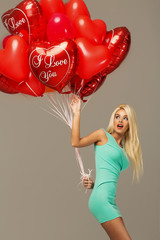 Blond beauty with red balloons heart