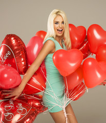 Blond cheerful woman with red balloons heart