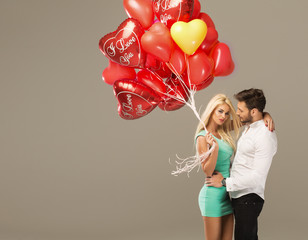 Happy loving couple on grey background with heart balloons