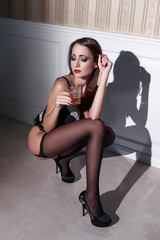 Sexy woman squat with alcohol at vintage wall