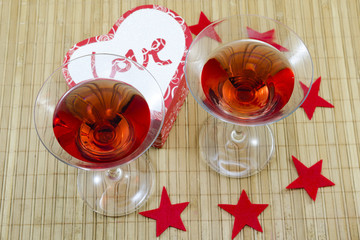 Two glasses with a red alcoholic drink and heart shaped candles