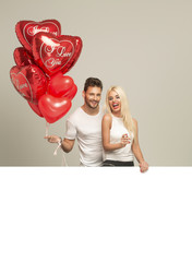 Young smiling couple with red balloons heart and white empty spa