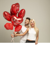 Young smiling couple with red balloons heart