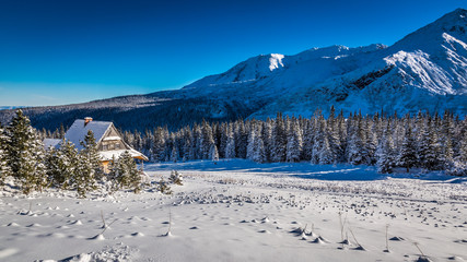 Small cottage at the foot of the mountains in winter