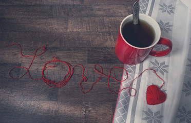 Red clews in shape of heart and cup on wooden back