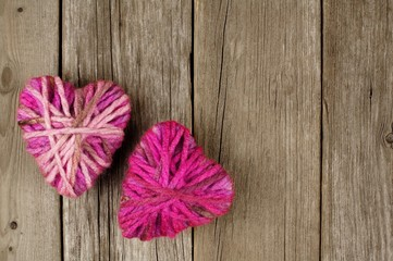 Valentines Day wool hearts against an old wood background