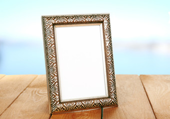 Photo frame on wooden table on blue background