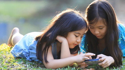 Asian girls playing a game on smartphone together in the park