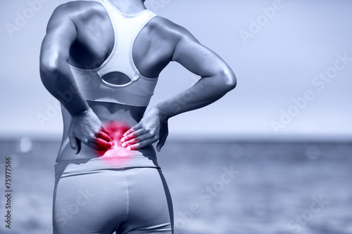 Back pain. Athletic running woman with back injury - 75977566