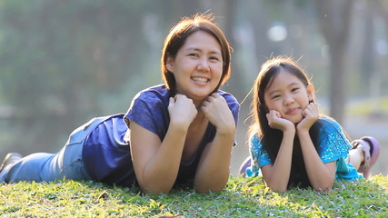 Happy Asian mother and daughter on grass at sunny summer day