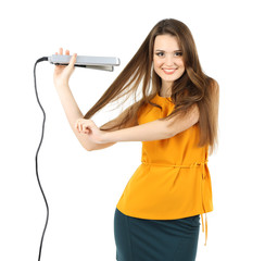 Beautiful young woman with long hair using hair straighteners