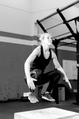 woman doing a box jump exercise - crossfit workout.