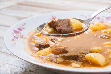 Traditional Hungarian goulash on spoon, closeup