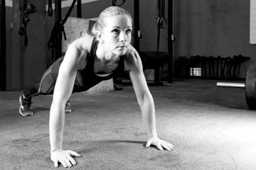 young woman making pushups - crossfit workout.
