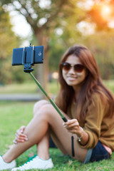 women hold monopod use smart phone take photograph selfie in par