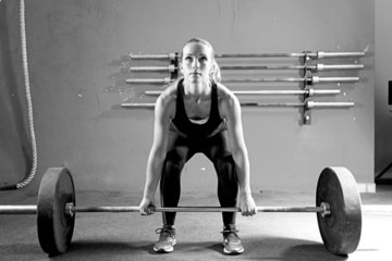 young woman on a weightlifting session - crossfit workout.