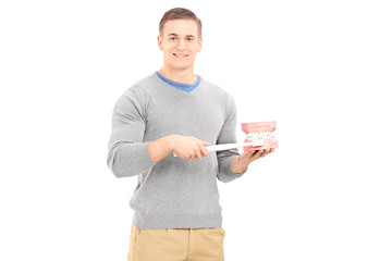 Young man holding a huge denture and toothbrush