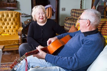 elderly couple singing and playing guitar