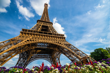 Wide shot of Eiffel Tower with dramatic sky and flowers