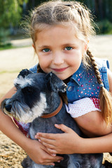 cute little american girl with a her dog for a walk
