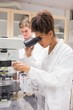 Pretty science student using microscope