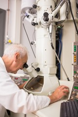 Biochemist using large microscope and computer