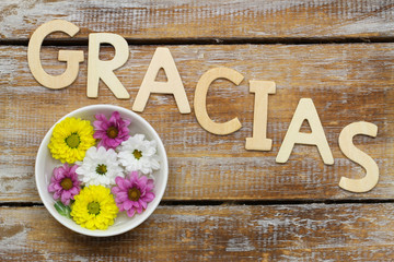 Word gracias (thank you in Spanish) and santini flowers
