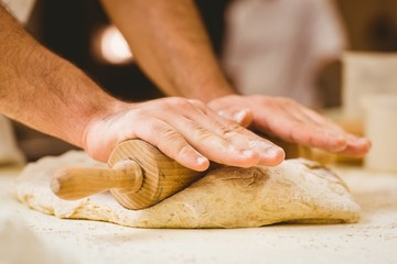 Baker rolling dough at a counter