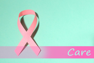 Pink breast cancer ribbon on turquoise background