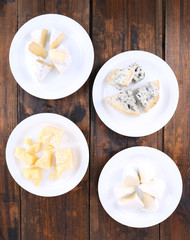 Various types of cheese on plates on wooden table background