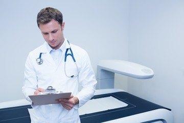 Doctor noting something on his clipboard