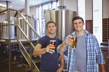 Young men holding a pint of beer smiling at camera