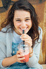 Teen girl drinking a fruit smoothie