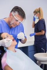 Dentist wearing face shield and examining a patient