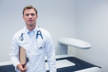 Happy doctor smiling at camera holding clipboard