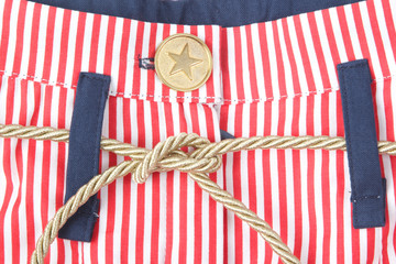Closeup of striped fabrics with a button and cord