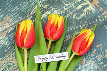 Happy birthday card with red and yellow tulips on rustic wood