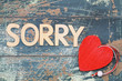 Leinwanddruck Bild - Sorry written with wooden letters on rustic wood, and red heart