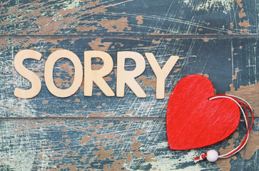 Sorry written with wooden letters on rustic wood, and red heart