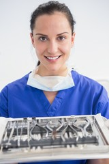 Smiling dentist holding tray with equipment
