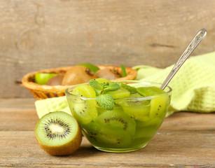 Tasty kiwi jam in glass bowl on wooden background