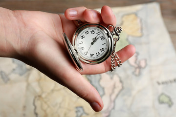 Silver pocket clock in hand closeup