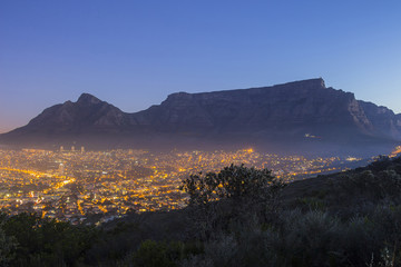 Table Mountain at dusk with city lights and blue sky
