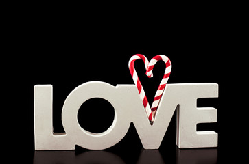 large letters LOVE and Heart Lollipop isolated on black - Stock