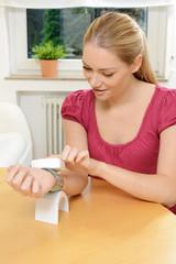 Frau misst Blutdruck und Puls mit Messgerät
