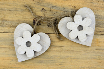 Two wooden hearts with a flowers on old wood