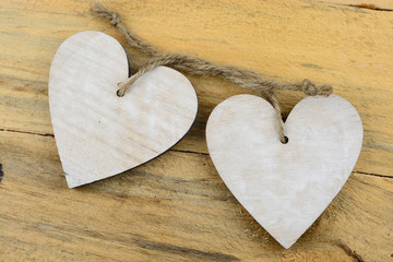 Two wooden hearts with on old wood holding with rope