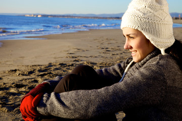 Happy young woman sitting in winter on the beach