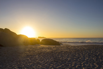 Sandy beach at sunset with rocks in the foreground