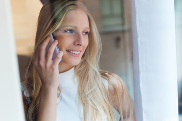 Young beautiful woman using her mobile phone at home.